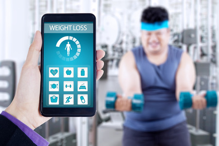 screen shot: Hand holding smartphone with weight loss monitoring application on the screen, shot with overweight person doing workout at gym