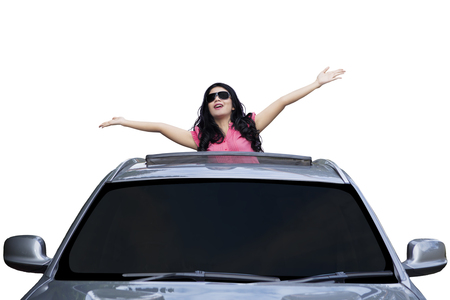 sunroof: Portrait of happy young woman celebrating her success by standing on the sunroof of the luxury car, isolated on white background Stock Photo