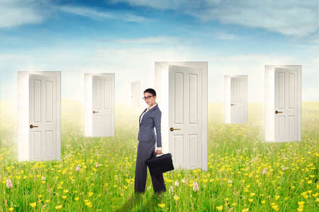 open business: Successful young businesswoman standing on the meadow in front of many open doors for business chance