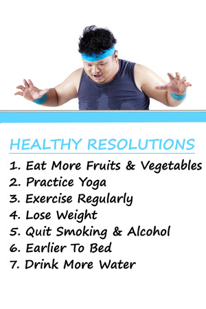 healthy looking: Overweight person wearing sportswear and looking at the list of healthy resolutions on the board