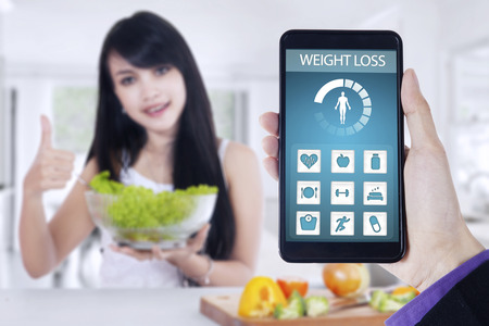 application icon: Close up of weight loss application on the mobile phone screen with young woman holding a bowl of salad