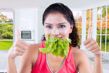 being: Picture of healthy Indian woman eats raw spinach while showing two thumbs up at the camera in the kitchen