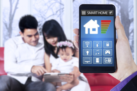 temperature controller: Close up of hand holding mobile phone with smart home applications on the screen and happy family sit on sofa at home Stock Photo