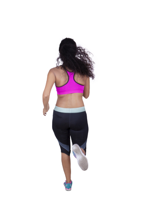 white back: Back view of female athlete running in the studio while wearing sportswear, isolated on white background