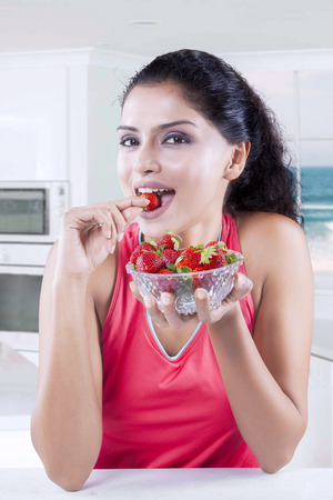 asian lady: Portrait of pretty Indian woman enjoy a bowl of fresh strawberry in the kitchen at home Stock Photo