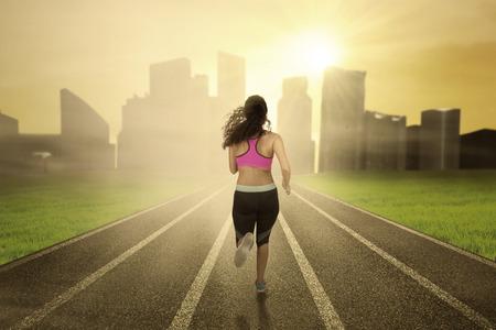 mujeres de espalda: Mujer corriendo en el campo mientras llevaba ropa deportiva hacia la ciudad en la mañana Foto de archivo