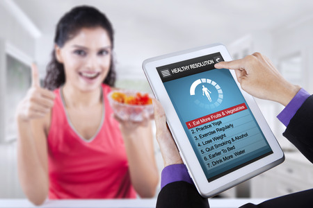 regularly: Image of hand holding digital tablet with list of healthy resolutions on the screen, shot with woman holding tomato