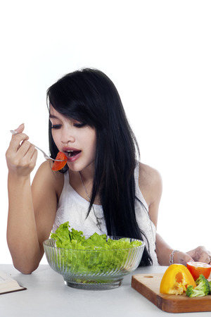 eating salad: Picture of pretty young Asian woman with long hair, eating a bowl of fresh salad on the table. Isolated on white background