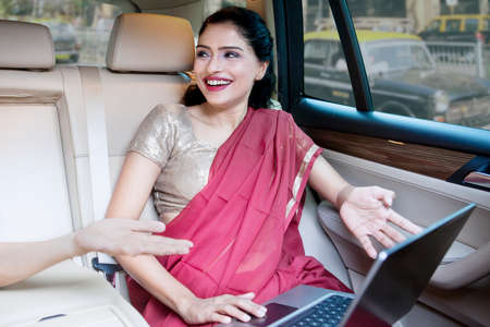 indian saree: Portrait of happy young businesswoman talking with her colleague while sitting in a car Stock Photo