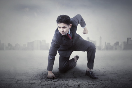 aggressive people: Portrait of angry male entrepreneur punching the ground, shot with city background