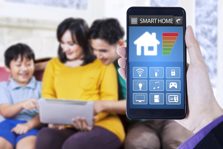 using smart phone: Close up of smart home application on the mobile phone, shot with happy family using tablet at home