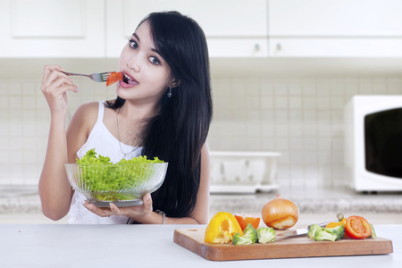 eating salad: Picture of healthy female model enjoying vegetable salad and biting tomato in the kitchen at home Stock Photo