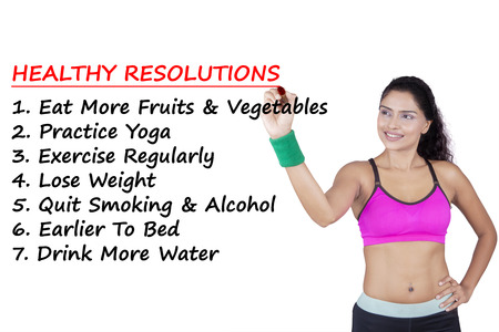 weight loss plan: Pretty Indian woman writes the list of healthy resolutions on whiteboard, isolated on white background