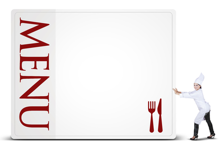 pushes: Portrait of female chef wearing a cooking wear and pushes a board of menu, isolated on white background