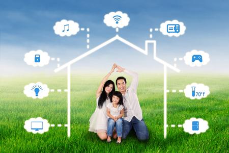 Foto der asiatischen Familie in der Natur sitzen, während ein Haus-Symbol unter Smart-Haus-Design machen