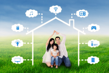 Photo of Asian family sitting in the nature while making a home symbol under smart house design