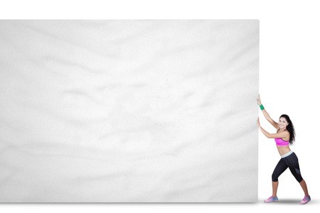billboard background: Image of fitness woman wearing sportswear and pushes a big empty billboard, isolated on white background