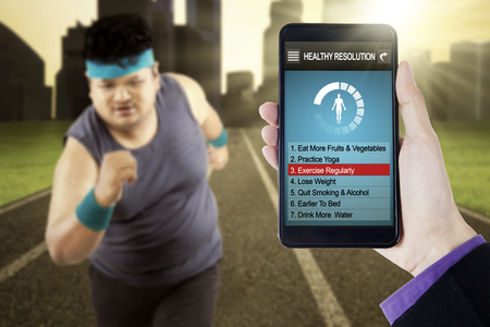 programs: Image of healthy resolutions program on the smartphone screen with overweight person running at field