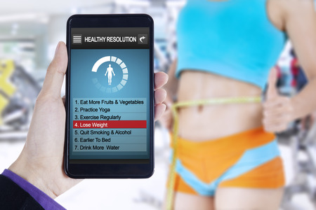 weight loss plan: Close up of the list of healthy resolutions on the mobile phone screen and slim woman measures her waist at gym