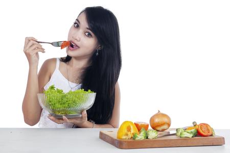 Portrait des schönen weiblichen Modell mit schwarzen Haaren, die eine Schüssel mit Gemüsesalat genießen. Isoliert auf weißem Hintergrund
