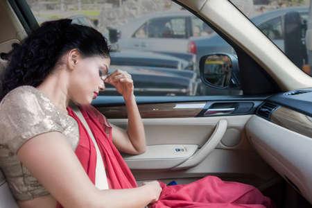 fille triste: femme indienne déprimé et assis dans la voiture avec la main sur la tête, tout en portant des vêtements traditionnels