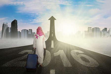 hombre arabe: empresario árabe con la maleta que recorre en la calle con el número 2016 de subir como una flecha, símbolo de la futura carretera Foto de archivo