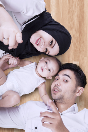 muslim baby: Unique perspective of muslim parents lying on the floor with their little baby while looking and smiling at the camera