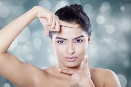 poses de modelos: Primer plano de modelo de mujer joven que enmarca su cara después de cuidado de la piel, un disparo en el estudio contra el fondo del bokeh Foto de archivo