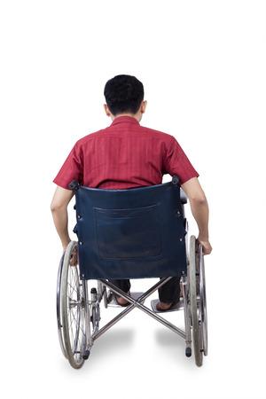 paraplegico: Vista posterior de la persona con discapacidad se sienta en la silla de ruedas, aislado en fondo blanco