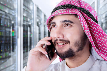 businessman phone: Closeup of Arabian male entrepreneur talking by mobile phone in office Stock Photo