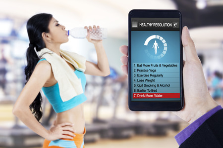 programs: Image of hand holding smartphone with healthy resolutions program on the screen and young woman drinking water at gym