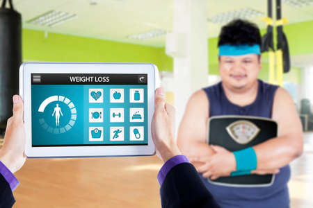heavy heart: Overweight person holding a scale at gym with weight loss applications on the digital tablet screen