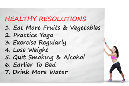 pushes: Young woman wearing sportswear pushes a big banner with healthy resolutions, isolated on white background Stock Photo