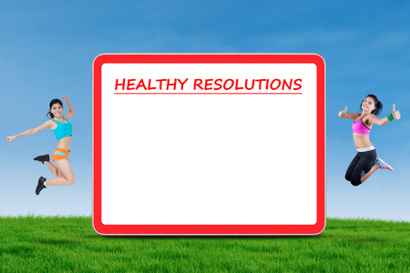 weight loss plan: Picture of two healthy female models jumping at the meadow near a billboard of healthy resolutions with copy space