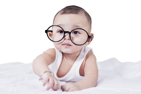 babies playing: Portrait of sweet baby boy lying on the bed while wearing glasses and looking at the camera