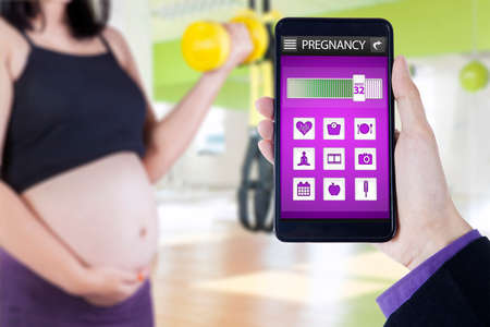 8 months pregnancy: Close up of pregnant mother doing exercise with dumbbell at gym and pregnancy app on the mobile phone screen Stock Photo
