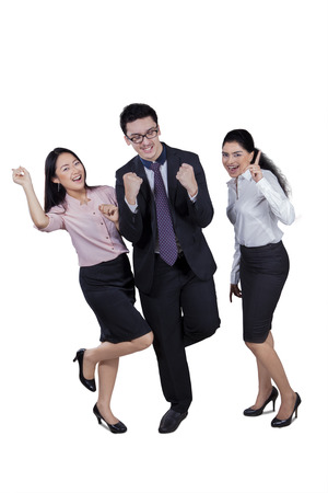 happy asian people: Three successful businesspeople celebrating a triumph with arms up in studio, isolated on white background
