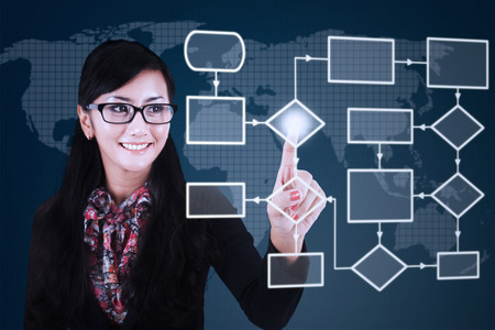 flow: Photo of a young businesswoman smiling at the camera while touching flow chart on the virtual screen