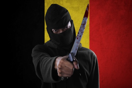 alarming: Picture of male terrorist using a bloody knife for threatening in front of Belgian flag
