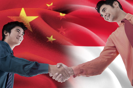 indonesian flag: Portrait of young Chinese entrepreneur shaking hands with Indonesian person in front of Chinese and Indonesian flags