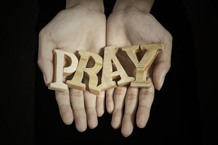 manos abiertas: Cerca de las manos de oración que muestra una palabra de rezar en fondo oscuro