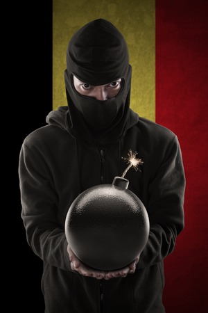 radical: Image of radical person wearing mask and menacing with a bomb in front of Belgian flag