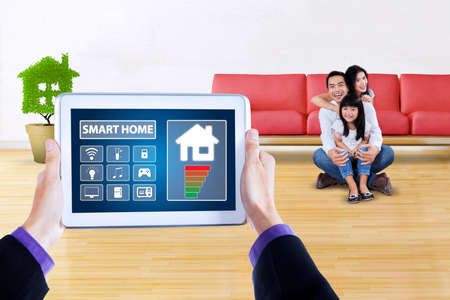 screen shot: Picture of modern applications of smart house system controller on tablet screen. Shot with happy family sitting at home Stock Photo