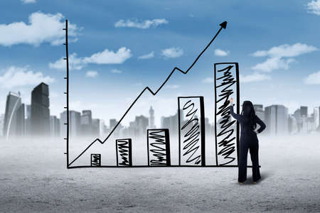 upward graph: Picture of a young businesswoman making a growing graph with upward arrow, shot outdoors