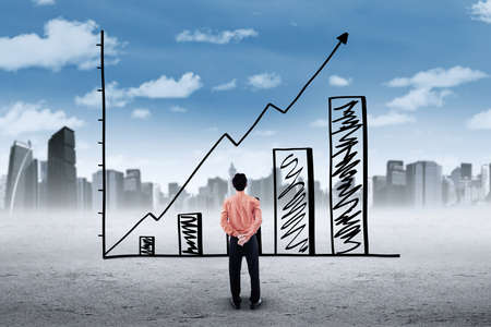 unemployment rate: Image of a young businessman looking at a growing chart with upward arrow, shot outdoors Stock Photo