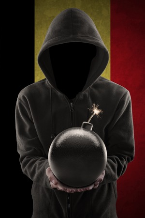 radical: Picture of radical person wearing mask and jacket while showing a bomb with Belgian flag background Stock Photo