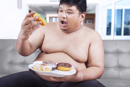 Portrait of asian man with fat body sitting on sofa while eating donuts Stock Photo