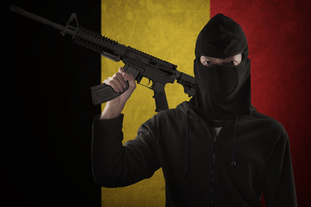 militant: Dangerous terrorist carrying a machine gun while wearing a mask in front of Belgian flag