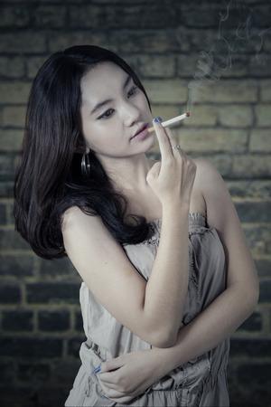 Portret van Aziatische tiener met vrijetijdskleding en lang haar, genietend van een sigaret