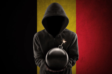 Dangerous terrorist wearing a hoodie and holding a bomb in front of Belgian flag Stock Photo